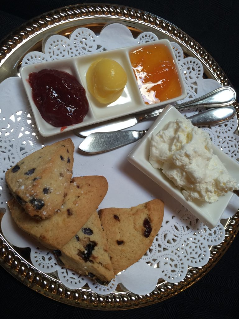 Scones of blueberry and cranberry are served with clotted cream, lemon curd and preserves