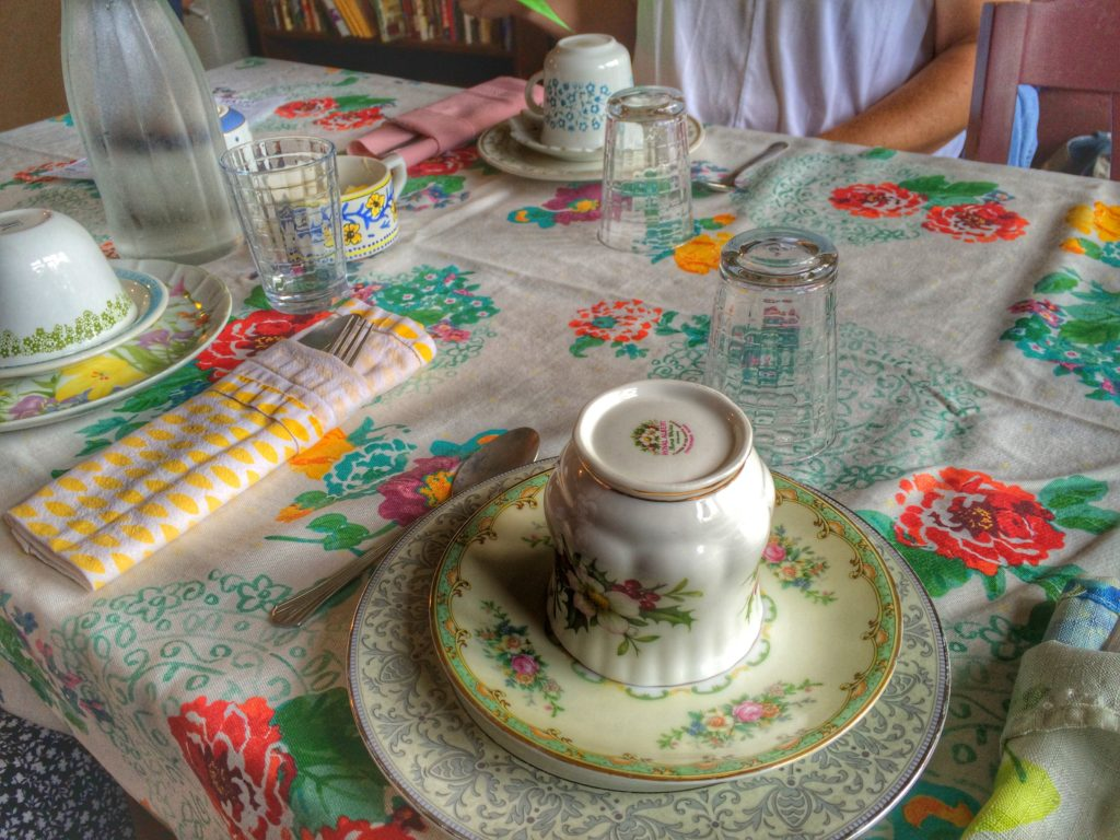 Mix-n-match china on a colorful tablecloth designate our high tea seating at one of Dr. Bombay's long communal tables.