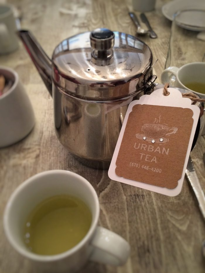 Tags tied to stainless steel pots label the pre-selected teas we pass around the table.