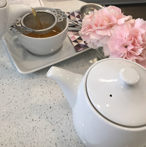 Pouring tea and carnations at Soirette afternoon tea