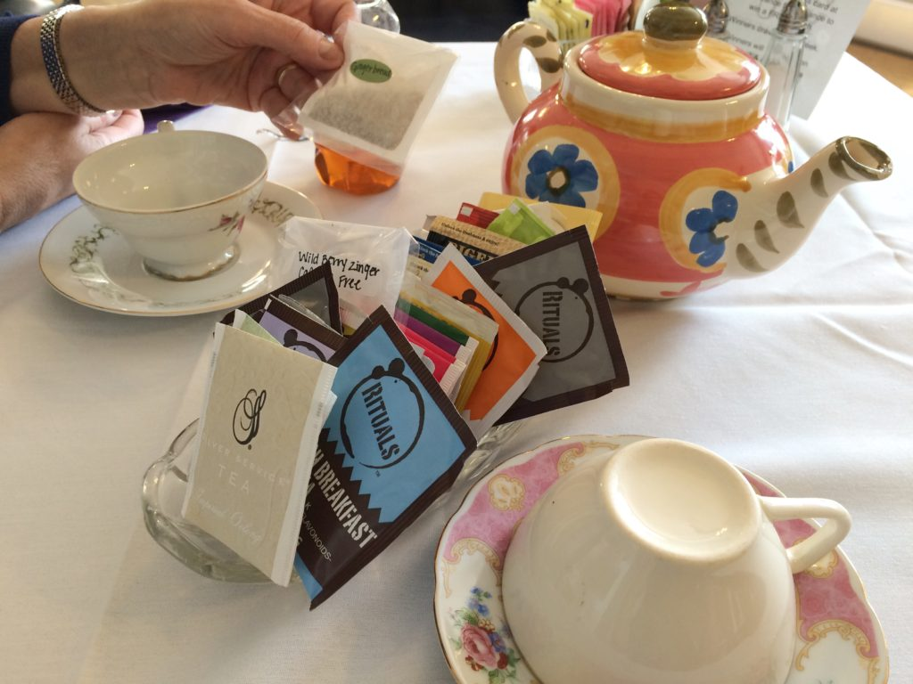 A selection of bagged teas is brought to the table with a pot of hot water.