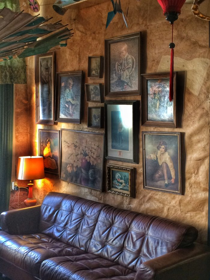 leather couch beneath framed artwork at Dr. Bombay's