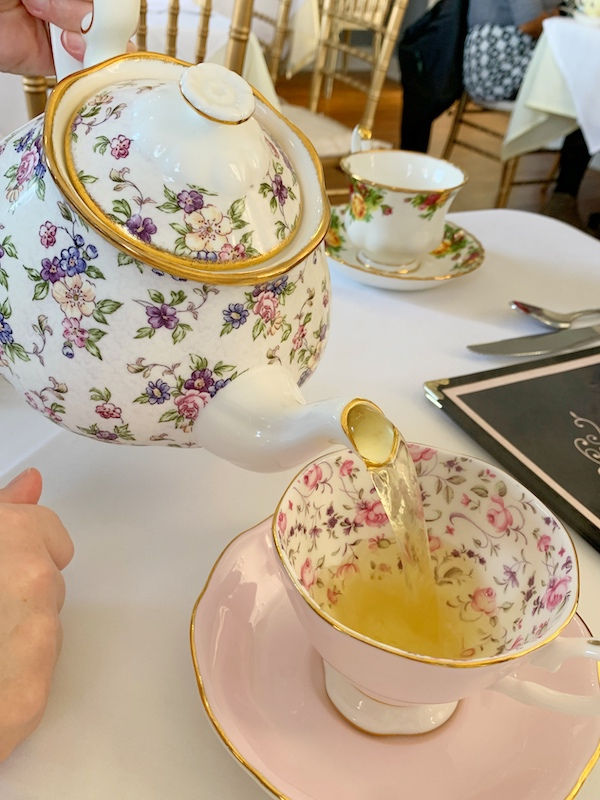 pouring tea at afternoon tea at Polly Claire's in Chattanooga, TN