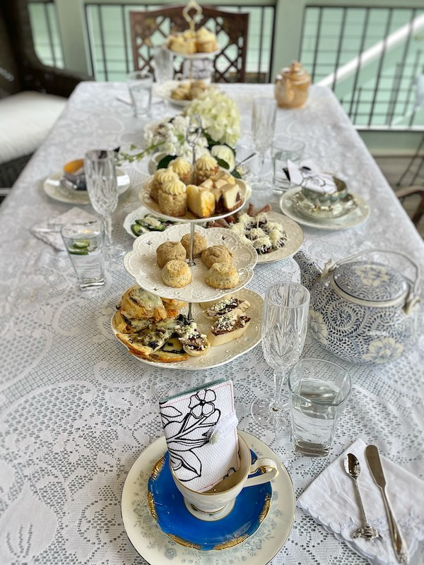 Tea wallets perch in teacups at this al fresco afternoon tea as favors