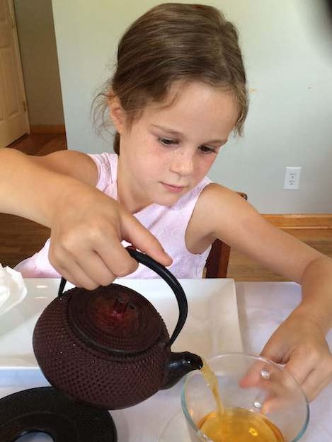 child pouring tea